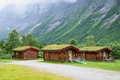 Norwegian wooden houses with grass on the roof at the foot of the mountain Royalty Free Stock Photo