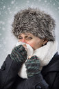 Nose blowing ill woman with warm clothes her under snow fall Stock Photography