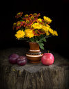 Nosegay of chrysanthemums and gayllardiyas with ri still life in country style mysterious night time lighting yellow red Royalty Free Stock Photography
