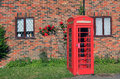 Nostalgic phone box in front of red brick wall with rambler rose Royalty Free Stock Photo