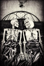 A not so dead romance halloween theme two skeletons in bed together textured Royalty Free Stock Image