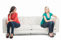 Not friends anymore two angry women looking at each other while sitting on the different sides of a couch Royalty Free Stock Images