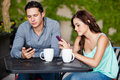 Not a great date young couple passing the time by using their cell phones on bad Royalty Free Stock Images