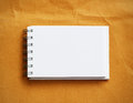 Note book mini on brown background Royalty Free Stock Photo