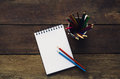 Note book and pencil colors on wooden Royalty Free Stock Photo
