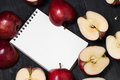 Notebook and apple on a black wooden background top view Royalty Free Stock Photo