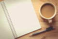 Notebook checked with a pencil and a cup of coffee. Royalty Free Stock Photo