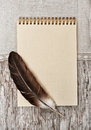 Notebook feather and linen fabric on the old wood paper spiral wooden background Stock Photos