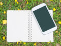 Notebook and mobile phone on green grass open cream with yellow flower background Royalty Free Stock Images
