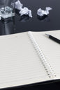 Notebook a open on the desk a pen on it some wastepapers can be seen Royalty Free Stock Photos
