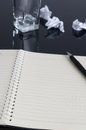 Notebook a open on the desk a pen on it some wastepapers can be seen Royalty Free Stock Photo
