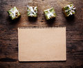 Notebook paper with gift box on wooden background Royalty Free Stock Images