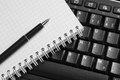 Notebook and pen on the black keyboard. Royalty Free Stock Photo