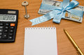 Notebook with pen, dollar bills, calculator and house key Royalty Free Stock Photo