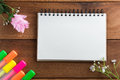 Notebook with a pen wooden floor highlights.