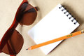 Notebook with pencil and sunglasses Royalty Free Stock Image