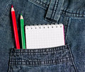 Notebook and pencils in jeans pocket with red green Royalty Free Stock Image