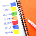 Notebook post it monday to sunday orange red pen and Royalty Free Stock Image