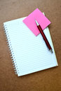 Notebook, red pen, pink note paper on wooden background. Royalty Free Stock Photo