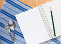 Notebook silver spoon and fork on blue cloth menu template Stock Image