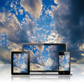 Notebook tablet pc and mobile phone over blue sky background Royalty Free Stock Images