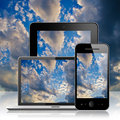 Notebook tablet pc and mobile phone over blue sky background Stock Images
