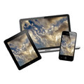 Notebook tablet pc and mobile phone with sunrise on a screen on white background Stock Image