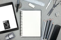 Notebook with various drawing tools and tablet with stylus on gr Royalty Free Stock Photo