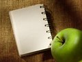 Notepad and apple on the sacking background Royalty Free Stock Images