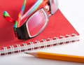 Notepad glasses and a pencil composition closeup Royalty Free Stock Photo