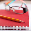 Notepad glasses and pencil composition a jotter closeup Royalty Free Stock Image
