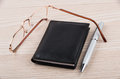 Notepad, pen and glasses on table Royalty Free Stock Photo
