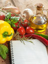 Notepad for recipes paper notes bottle of olive oil tomatoes mushrooms onion pepper condiments and basil on a wooden table Royalty Free Stock Photo