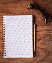 Notepad with a spiral binding on wood table Royalty Free Stock Images