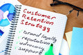 Notepad with words  customer retention strategies. Royalty Free Stock Photo