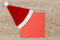 Notepaper with santa hat on wood Royalty Free Stock Photo