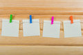 Notes on color clothespin hanging with blank paper wooden background Royalty Free Stock Images