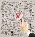 Nothing is impossible concept businessman hand holding magnifier over red checkmark with business drawings around on crumpled Stock Photos