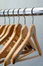 Nothing to wear empty wooden hangers hanging on a shiny metal bar Stock Image