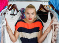 Nothing to wear and hard to decide concept beautiful smiling blonde woman standing inside wardrobe rack full of clothes suffering Royalty Free Stock Images