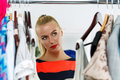 Nothing to wear and hard to decide concept thoughtful beautiful blonde woman standing near wardrobe rack full of clothes choosing Royalty Free Stock Images