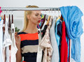 Nothing to wear and hard to decide concept thoughtful beautiful blonde woman standing near wardrobe rack full of clothes choosing Stock Image