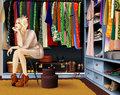 Nothing to wear sad girl is choosing clothes she sitting near her clothes rack in wardrobe with lots of dresses shoes hatboxes and Royalty Free Stock Images