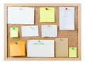 Notice board with blank messages a cork pinboard isolated on white a variety of pushpins sticky notes cards and pieces of paper Stock Photography