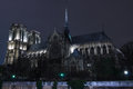 Notre dame cathederal at night viewed from the banks of the river seine Royalty Free Stock Images