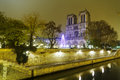 Notre dame de paris over the seine river at night france Stock Image