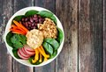Nourishment bowl with quinoa, hummus, mixed vegetables, over rustic wood Royalty Free Stock Photo