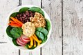 Nourishment lbowl with quinoa, hummus, mixed vegetables, over white wood Royalty Free Stock Photo