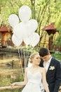 Nouveaux mariés en stationnement avec des ballons Image stock