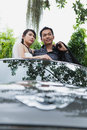 Novia y novio smiling together while que se coloca en coche Fotografía de archivo